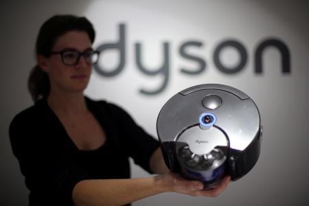展示会でロボット掃除機を見せるダイソンの従業員=2014年9月(ロイター=共同)