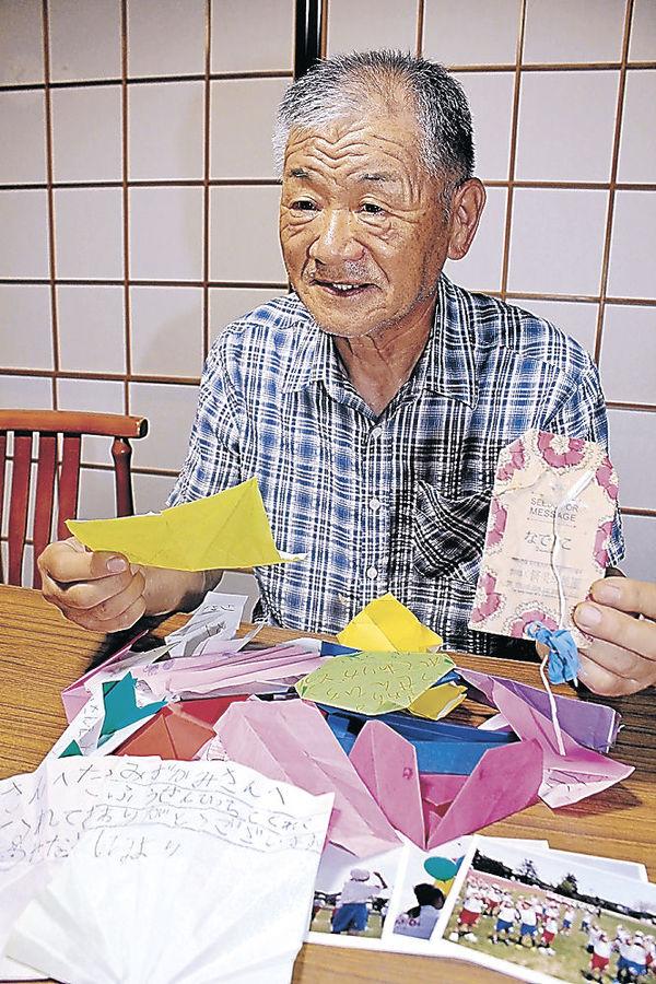 見つけた風船を手に、園児のメッセージや写真に目を通す水上さん=南砺市信末