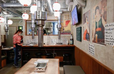 客もなく閑散とする東京・新橋の飲食店。オーナーの女性は「明日からは午後8時の閉店に応じる」と話した=7日午後7時22分