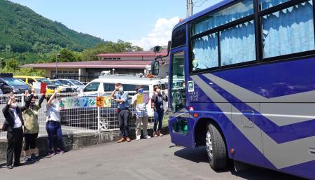 再建された「津久井やまゆり園」に入所する利用者を乗せたバスを出迎える職員ら=1日午前、相模原市