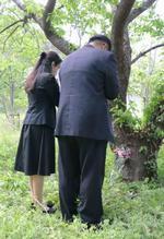 20日の命日を前に、息子の自殺現場で手を合わせる両親=18日、長崎市