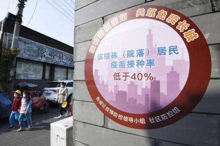居住区の壁に掲示された住民のワクチン接種率。「40%未満」と書かれている=8日、北京(共同)