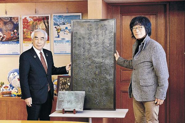 歌碑銅板を引き渡した尾竹さん(右)=高岡市役所