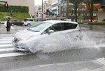 金沢で局地的な雨・水しぶきをあげて走行する車=22日午後4時15分 金沢市の香林坊交差点