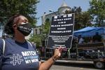 22日、米ワシントンで新型コロナウイルス関連の失業対策を求めるデモにマスク姿で参加する女性(ロイター=共同)