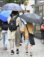 東京・渋谷で傘を差して歩く人たち=14日午前