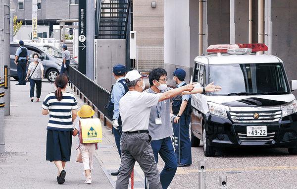 警察官や教諭が見守る中、保護者と一緒に帰宅する児童=富山市五福小
