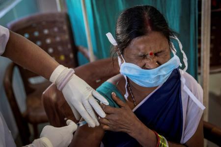インドで生産された新型コロナウイルスワクチンの接種を受ける女性=1月16日、インド東部(ロイター=共同)