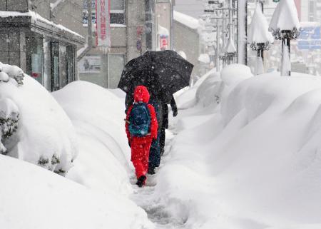 雪が積もった富山市内を歩く人たち=9日午前