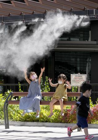 台風一過の晴天で気温が上がり、東京・銀座でミストを浴びる子どもたち=19日午後