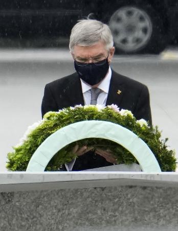 7月16日、平和記念公園を訪問し、原爆慰霊碑に献花するIOCのバッハ会長=広島市