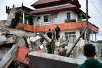 15日、インドネシア・西スラウェシ州の建物倒壊現場で、生存者を捜索する救助隊(AP=共同)