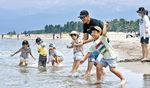 波打ち際で涼をとる家族=富山市の岩瀬浜海水浴場