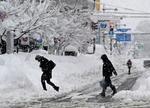 雪が積もった富山市内を歩く人たち=10日