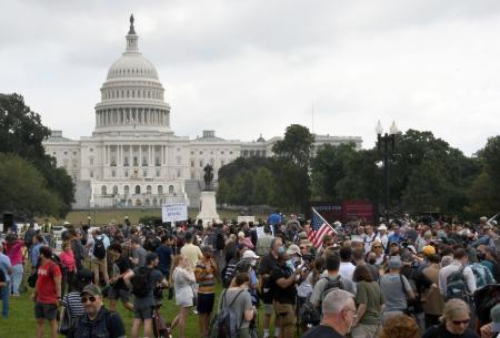 米連邦議会議事堂前の広場で開かれた右派の集会に参加した人たち=18日、ワシントン中心部(共同)