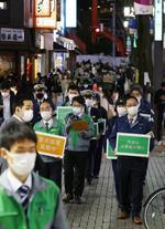 東京都新宿区の繁華街で外出自粛などを呼び掛ける都や区の職員ら=12日夜