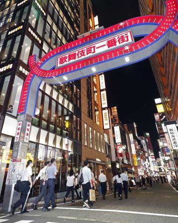 東京・新宿の歌舞伎町で、風営法に基づく立ち入り調査に向かう警視庁の捜査関係者と新型コロナウイルスの感染予防策の実施状況の確認に向かう都職員ら=24日夜