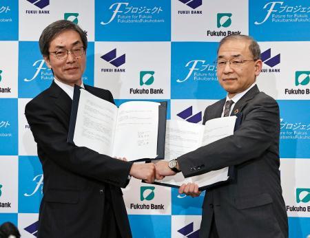 基本合意の文書を手に撮影に応じる、福井銀行の林正博頭取(左)と福邦銀行の渡辺健雄頭取=14日午後、福井市