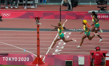 女子100メートル決勝 10秒61の五輪新で優勝したジャマイカのエレーン・トンプソンヘラ(左)=国立競技場
