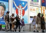 大阪・ミナミを歩くマスク姿の人たち。新型コロナウイルス感染の急拡大を受け、大阪府は政府に対し緊急事態宣言発令を要請する=19日夕