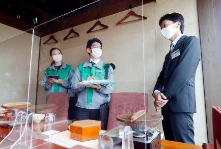 飲食店を訪問し、アクリル板の設置状況など新型コロナウイルス感染防止対策の確認をする見回りチームの担当者=12日午後、東京都新宿区