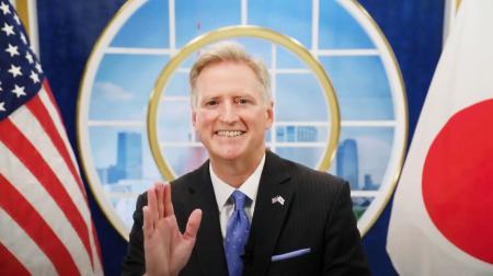 ビデオメッセージで手を振るジョセフ・ヤング駐日臨時代理大使(在日米大使館のユーチューブから、共同)
