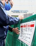 福岡市中心部の警固公園に設置された柵に、立ち入り制限のお知らせを取り付ける市職員=1日午前
