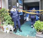 女性が殺害された店が入るビル前の警察官と手向けられた花束=16日午前、大阪市
