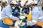 傷病者を運ぶ消防隊と救急隊=4日午前10時10分、金沢市三池町の駅西消防署小坂出張所