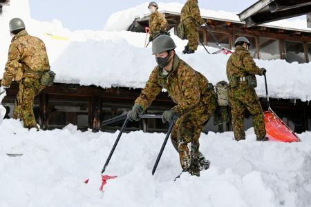 秋田県横手市の市立栄小で、屋根の雪を下ろす自衛隊員=7日午前