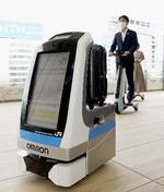 JR東日本が実証実験する、手荷物を運ぶロボット。奥はパーソナルモビリティー=27日午前、東京都港区の高輪ゲートウェイ駅