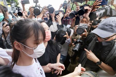 12日、香港の刑務所を出所し報道陣に取り囲まれる民主活動家、周庭氏(共同)
