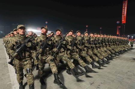 平壌の金日成広場で行われた軍事パレードで行進する兵士=14日(朝鮮中央通信=共同)