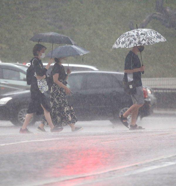 激しい雨が降る中目的地へ向かう人=22日午後3時40分 金沢市香林坊2丁目