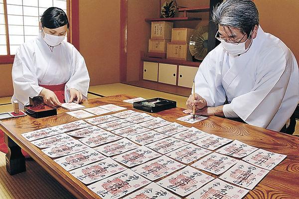 「桜詣」の御朱印を準備する神職と巫女=南砺市の髙瀬神社