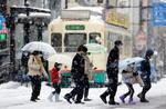 雪が降り続く富山市内を歩く人たち=2日午後