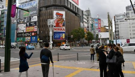札幌市の繁華街、ススキノを行き交う人たち=13日午後