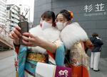東京23区では唯一の開催となった、杉並区の「成人祝賀のつどい」会場前で記念撮影する新成人=11日午前