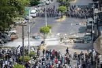 28日、ミャンマー・ヤンゴンで警察の治安部隊(奥)とにらみ合うデモ参加者(ロイター=共同)