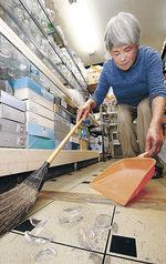 割れたガラスの皿を片付ける店員。商品が床一面に散らばるほどの被害はなかった=17日午前9時半、珠洲市飯田町