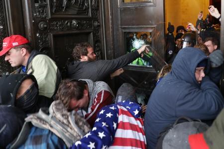 6日、米ワシントンの連邦議会議事堂内に侵入しようとするトランプ大統領の支持者ら(ゲッティ=共同)