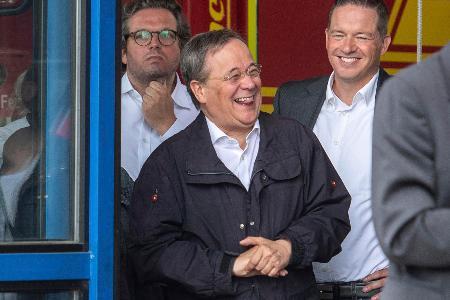 ドイツ西部ノルトライン・ウェストファーレン州の被災地訪問中、笑うラシェット州首相(中央)=17日(AP=共同)