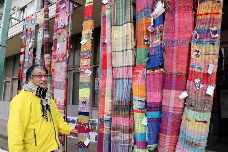 展示された「さをり織り」の作品とツナミクラフト代表の東山高志さん=16日午前、兵庫県西宮市