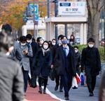 仕事始めを迎えた4日朝、マスク姿で職場に向かう人たち=東京・霞が関